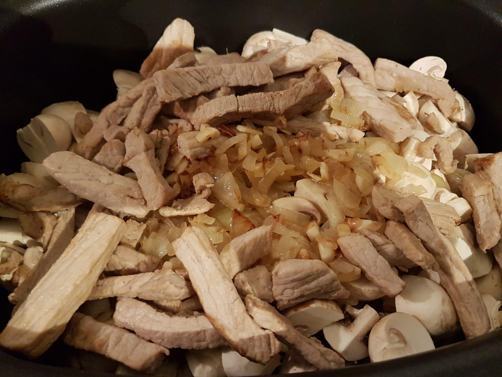 Fleisch, Pilze, Knoblauch und Zwiebeln im Slow Cooker.