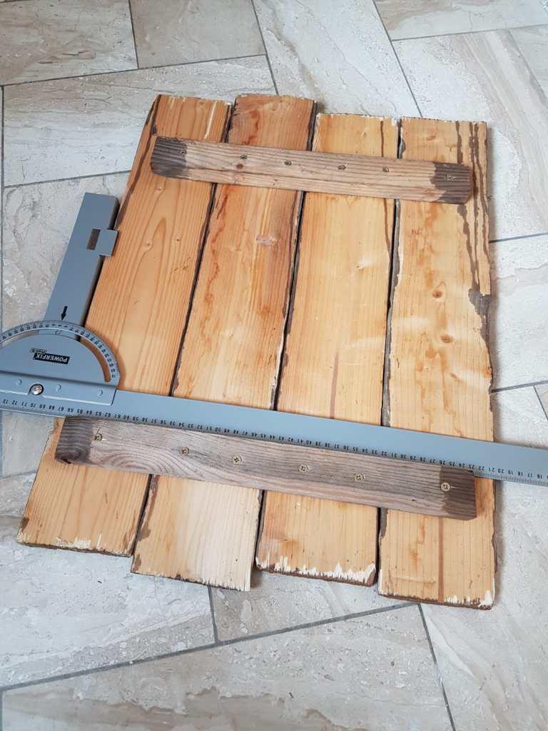 Die Altholzbretter der Sylt Wanduhr werden ausgerichtet und verschraubt.